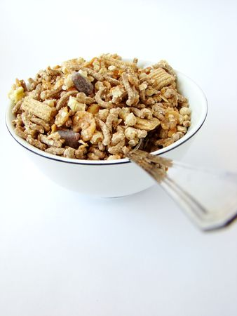 Cup of cereals with spoon on white background.
