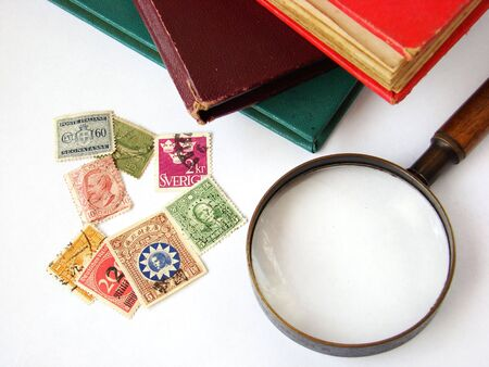 World postage stamps and magnifying glass on white background with books