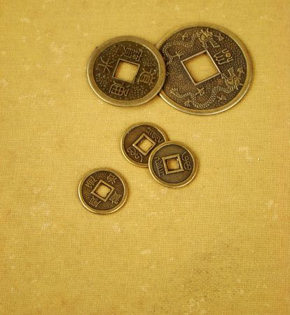 Chinese feng shui coins for good fortune and success in old and worn textile background