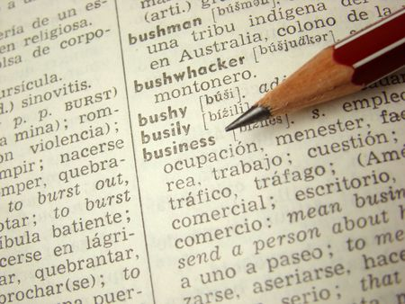 business word in english-spanish dictionary with pencil                                Stock Photo