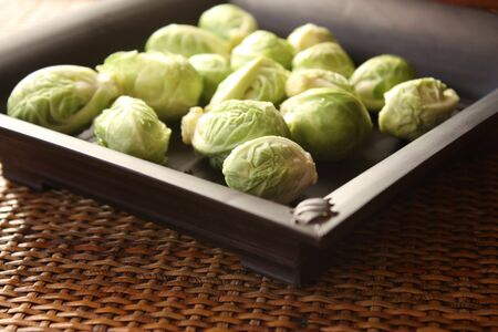 Fresh brussels sprouts on black plate - selective focus