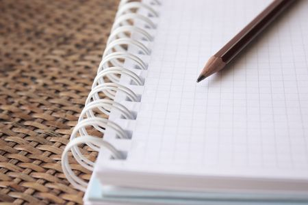 Spiral bound notebook with pencil over rattan desk- shallow dof Stock Photo - 6678787