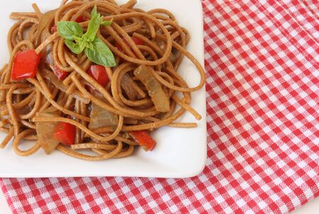 Pasta with vegetables and basil over checkered tablecloth photo