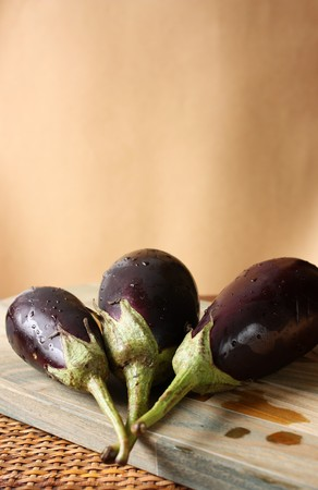 Fresh Baby Eggplants over cutting board - space for text Stock Photo