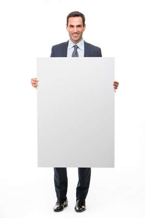 25 years old: Full length portrait of a smiling businessman holding a white placard Stock Photo