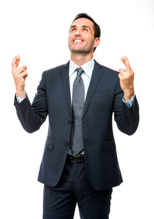 Half length portrait of a businessman smiling, looking above with his fingers crossed photo