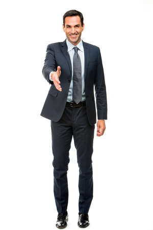 25 to 30 years old: Full length portrait of a businessman smiling raising his arm for shaking hands Stock Photo