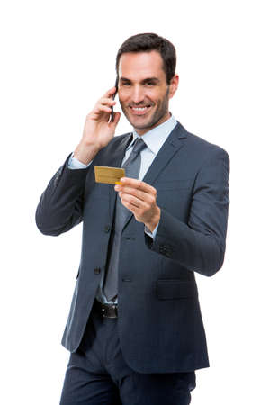 25 30 years old: Half length portrait of smiling businessman on the phone holding a credit card Stock Photo