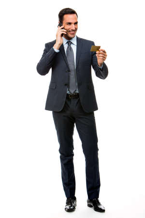 25 30 years old: Full length portrait of smiling businessman on the phone holding a credit card