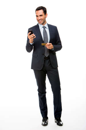 25 to 30 years old: Full length portrait of a smiling businessman holding mobile phone and credit card