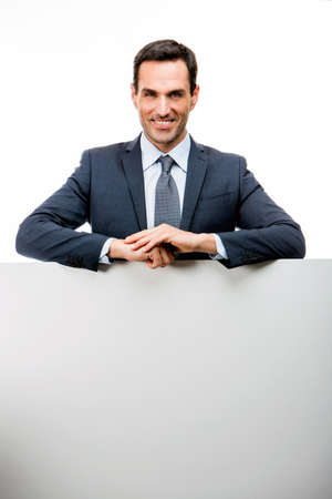 25 30 years old: Half length portrait of a smiling businessman leaning on a white placard Stock Photo