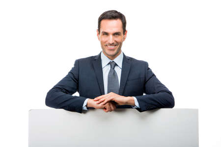 25 to 30 years old: Half length portrait of a smiling businessman leaning on a white placard Stock Photo
