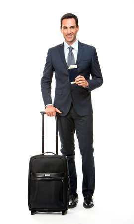 30 to 35 years old: Full length portrait of a smiling businessman with trolley and holding his passport Stock Photo
