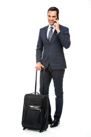 25 to 30 years old: Full length portrait of a smiling businessman with trolley talking on the phone Stock Photo