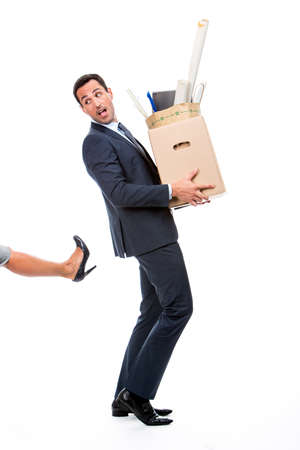 two persons only: Full length portrait of a businessman carrying a cardboard box and being kicked Stock Photo