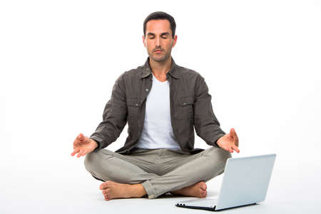 sitted: Man sitted on the floor with eyes closed practicing yoga with laptop next to him