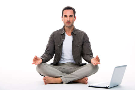 25 to 30 years old: Man sitted on the floor looking at the camera and practicing yoga with laptop next to him Stock Photo