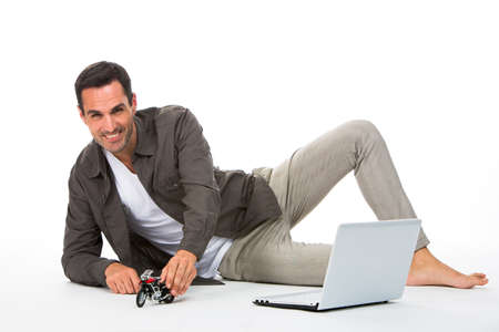 25 to 30 years old: Man laying on the floor, smiling at camera playing with a motorbike scale model and laptop next to him