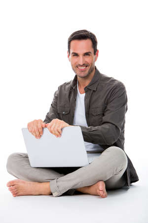 sitted: Man sitted on the floor, smiling at camera, holding his laptop with both hands Stock Photo