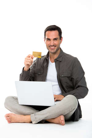 sitted: Man sit on the floor, showing credit card and buying online