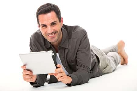 25 30 years old: Man laying on the floor, smiling at camera and holding his digital tablet with both hands
