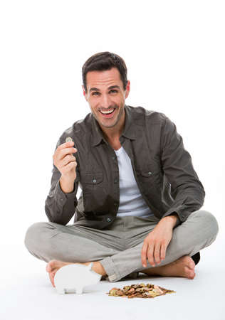 sitted: Man sitted on the floor, smiling at camera, holding a coin Stock Photo