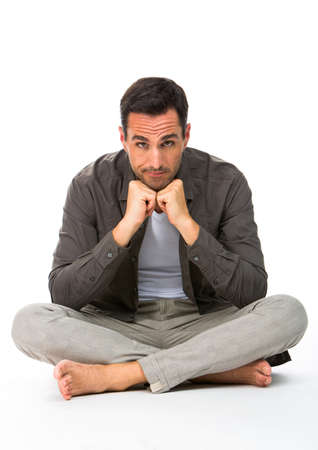 Thoughtful man sitted on the floor, looking at camera, with the hands under his chin photo