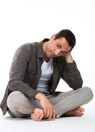 sitted: Thoughtful man sitted on the floor, looking at camera and holding his head with one hand