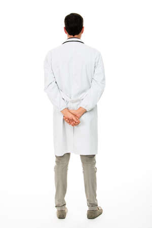 in the back: Full length backside view of a male doctor with hands behind his back Stock Photo