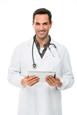 25 30 years old: Half length portrait os a smiling male doctor with stethoscope and holding a dital tablet Stock Photo