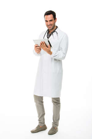 25 30 years old: Full length portrait os a smiling male doctor with stethoscope while working with a dital tablet