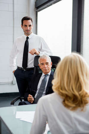50 to 55 years old: Three businesspeople having a meeting in the office