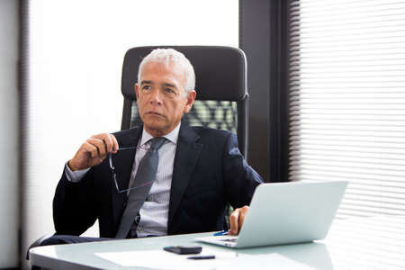 50 to 55 years: Half length portrait of a thoughtful businessman in the office with laptop computer and holding glasses Stock Photo