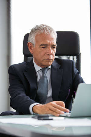 50 to 55 years old: Half length portrait of a thoughtful businessman in the office while using laptop computer