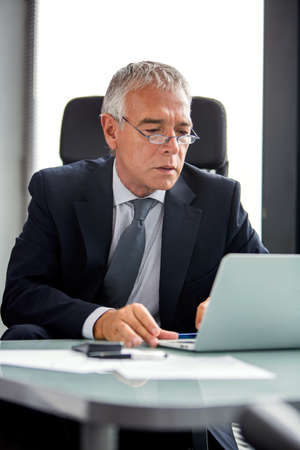 50 to 55 years: Half length portrait of a thoughtful businessman in the office while using laptop computer