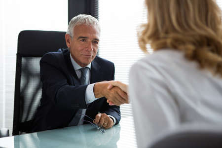 50 to 55 years: Two businesspeople, male and female, shaking hands during a meeting in the office Stock Photo