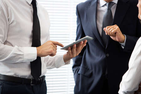 Half lenght portrait of two businessmen talking and using a digital tablet