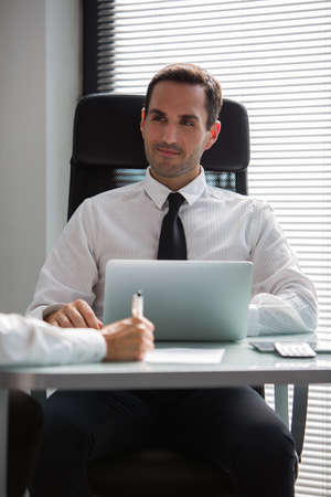 Two businesspeople having a meeting in the office using laptop computer photo