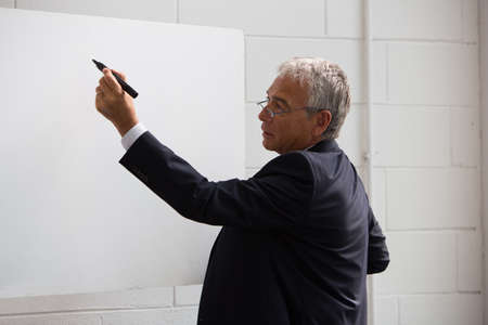 Half length portrait of a businessman wrtiting on a blank billboard with a black marker photo