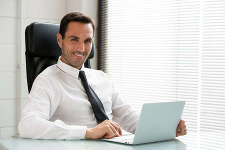 Half length portrait ofa male businessman, smiling at camera and working with a laptop computer