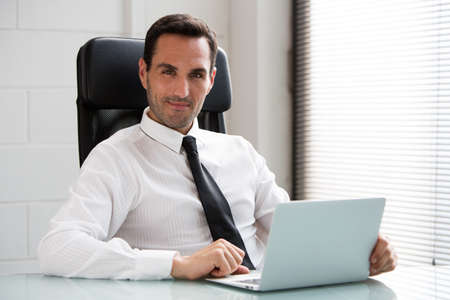 25 to 30 years old: Half length portrait of a male businessman in the office, looking at camera and working with a laptop computer Stock Photo