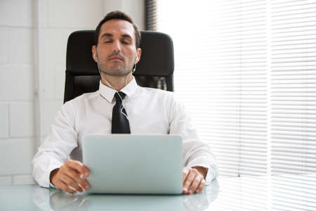 25 30 years old: Half length portrait of a male businessman with eyes closed, earphones and laptop computer Stock Photo