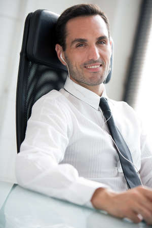 25 30 years old: Half length portrait of a male businessman with earphones, smiling at camera Stock Photo
