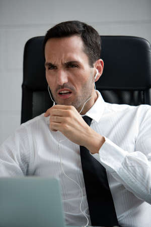 25 to 30 years old: Half length portrait of a angry male businessman with earphones and laptop computer Stock Photo