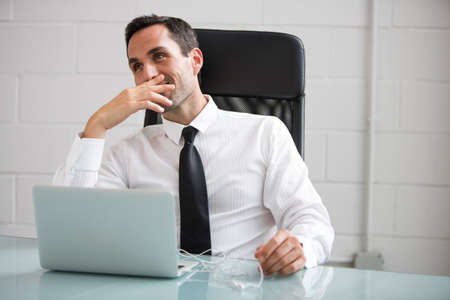 30 to 35 years old: Half length portrait of a male businessman with earphones and laptop computer