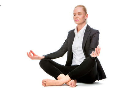 sitted: blonde businesswoman sitted on the floor doing a yoga position with her eyes closed Stock Photo