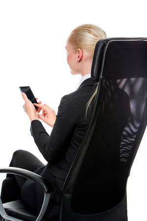25 to 30 years old: blonde smiling businesswoman seated on a chair with mobile phone