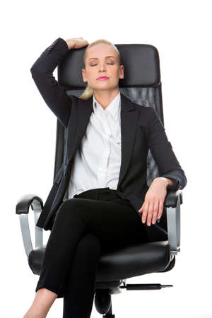 25 to 30 years old: blonde smiling businesswoman relaxing on a chair with eyes closed