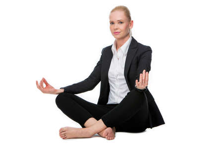 25 to 30 years old: blonde businesswoman seated on the floor doing a yoga position Stock Photo