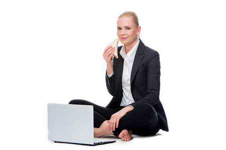 25 to 30 years old: blonde businesswoman seated on the floor with computer and eating a sandwich Stock Photo